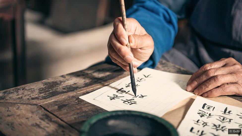شخص متقدم بالعمر يستخدم أدوات تقليدية من الحبر والفرشاة لكتابة الخط الآسيوي