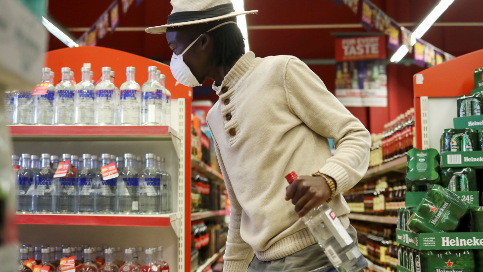 A man holding a vodka bottle in supermarket in Soweto, South Africa - June 2020