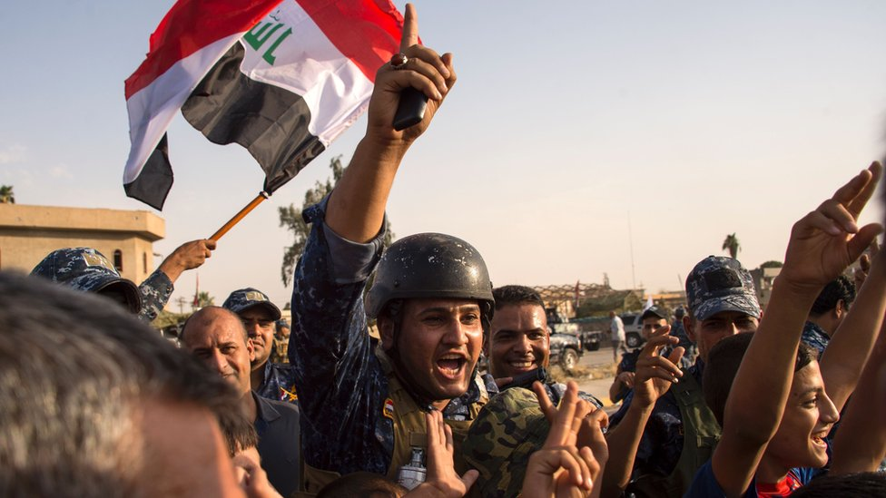 Iraq's federal police wave the national flag as they celebrate in the Old City of Mosul, 9 July 2017