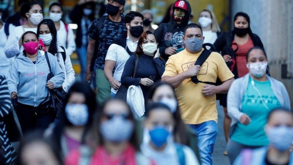 Pessoas de máscara na rua em São Paulo