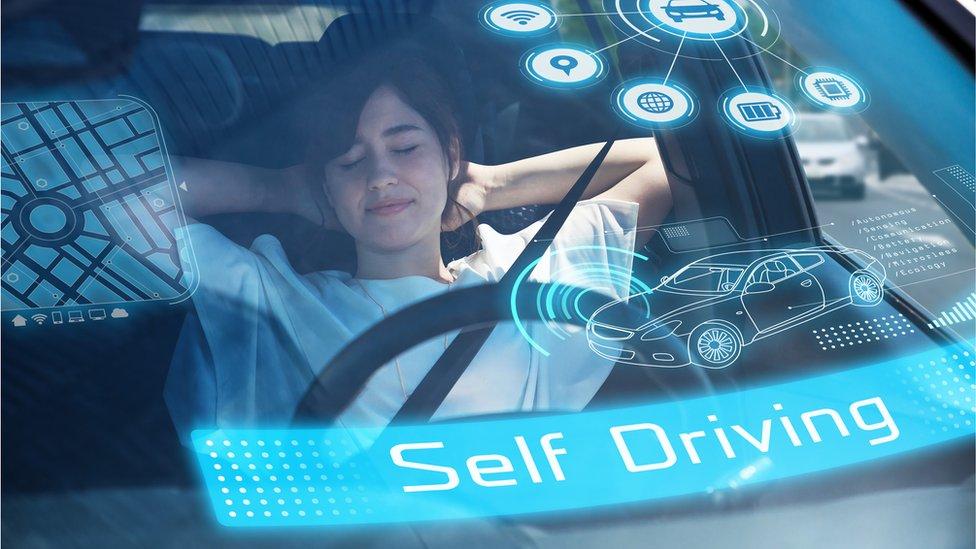 Woman asleep at wheel of futuristic self-driving car