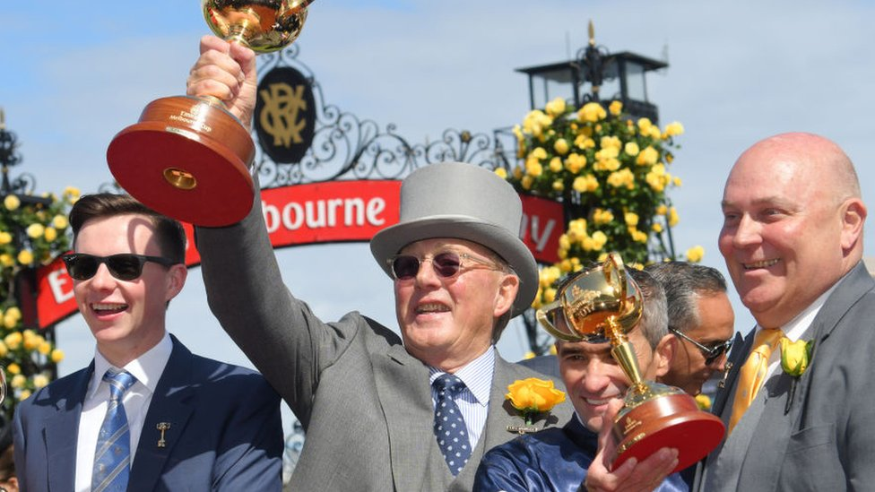 Horse owner Lloyd Williams (middle) holds up the Melbourne Cup trophy with colleagues after his horse Rekindling won the 2017 race