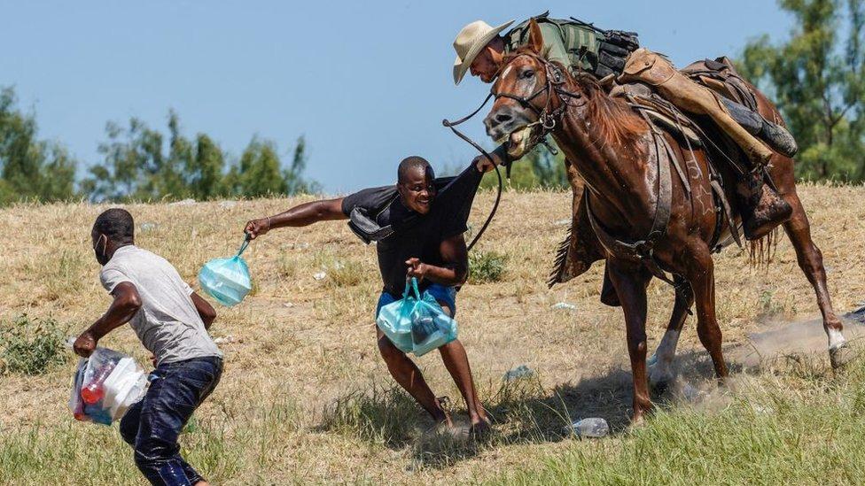 Un agente fronterizo a caballo agarra a un migrante en Texas.