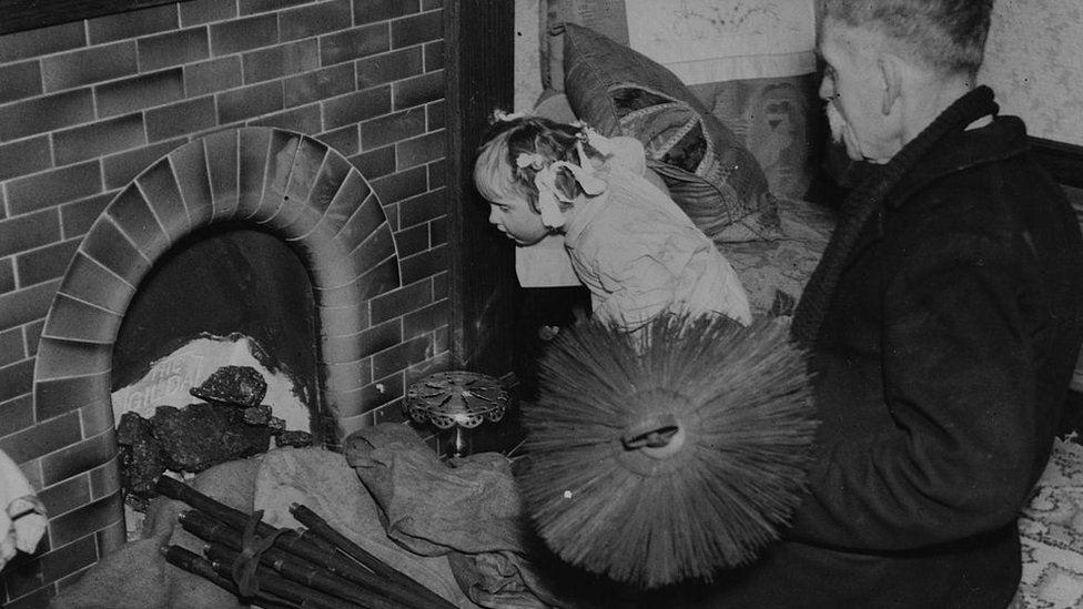 A chimney sweep at work with his brushes in 1937