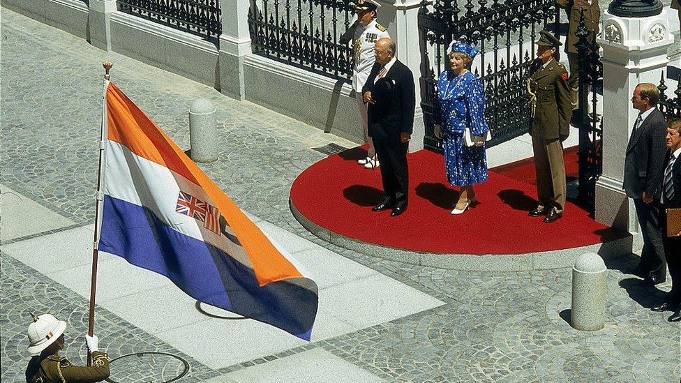 El expresidente sudafricano Pieter Willem Botha y su esposa Elize se paran frente al edificio del Parlamento en Ciudad del Cabo durante la apertura estatal del Parlamento en 1987. La bandera que flamea es la antigua insignia de la República de Sudáfrica, utilizada desde 1928-1994.
