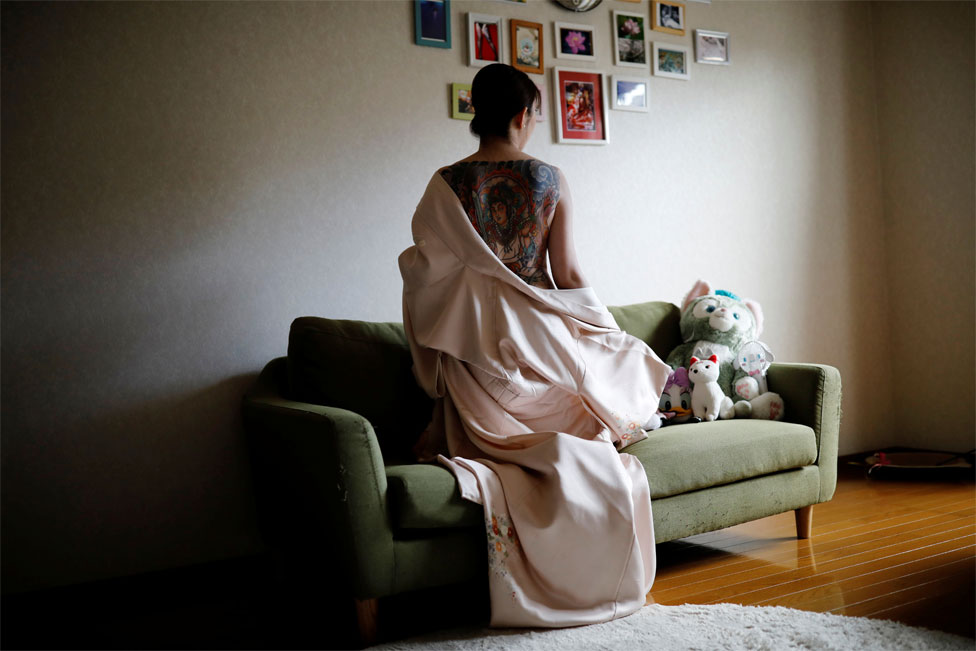 A woman kneels on a couch with a garment pulled down to reveal her large back tattoo to the camera