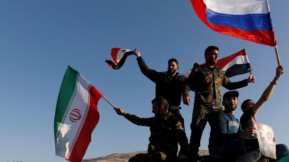 Sirios ondean banderas de Irán, Rusia y Siria después de los ataques contra Siria.