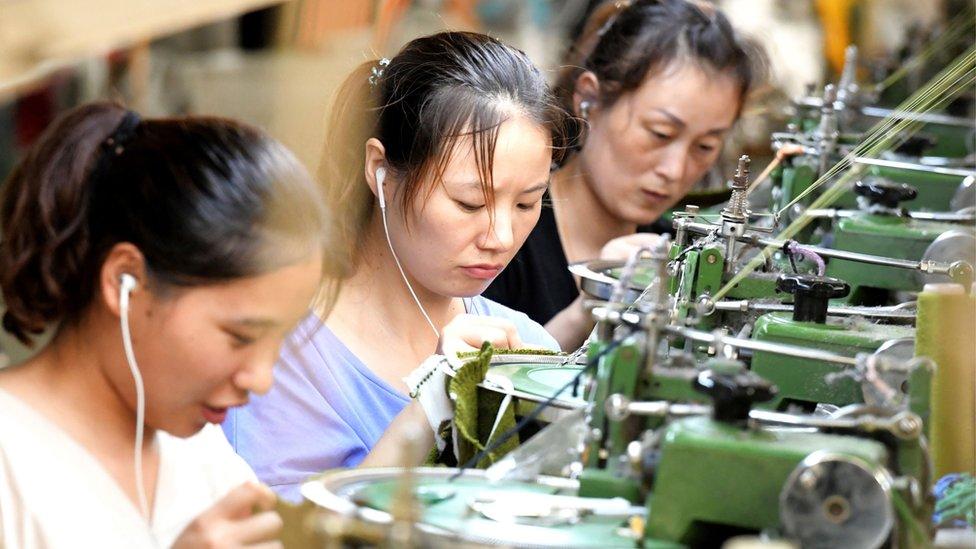 Empleados trabajan en una línea de producción de ropa para la exportación en China.