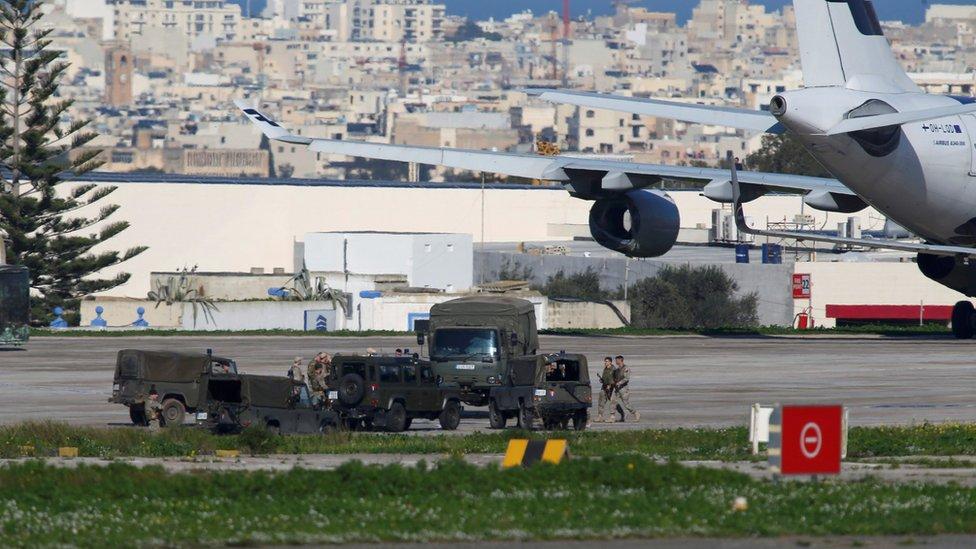 Maltese troops survey a hijacked Libyan Afriqiyah Airways Airbus A320