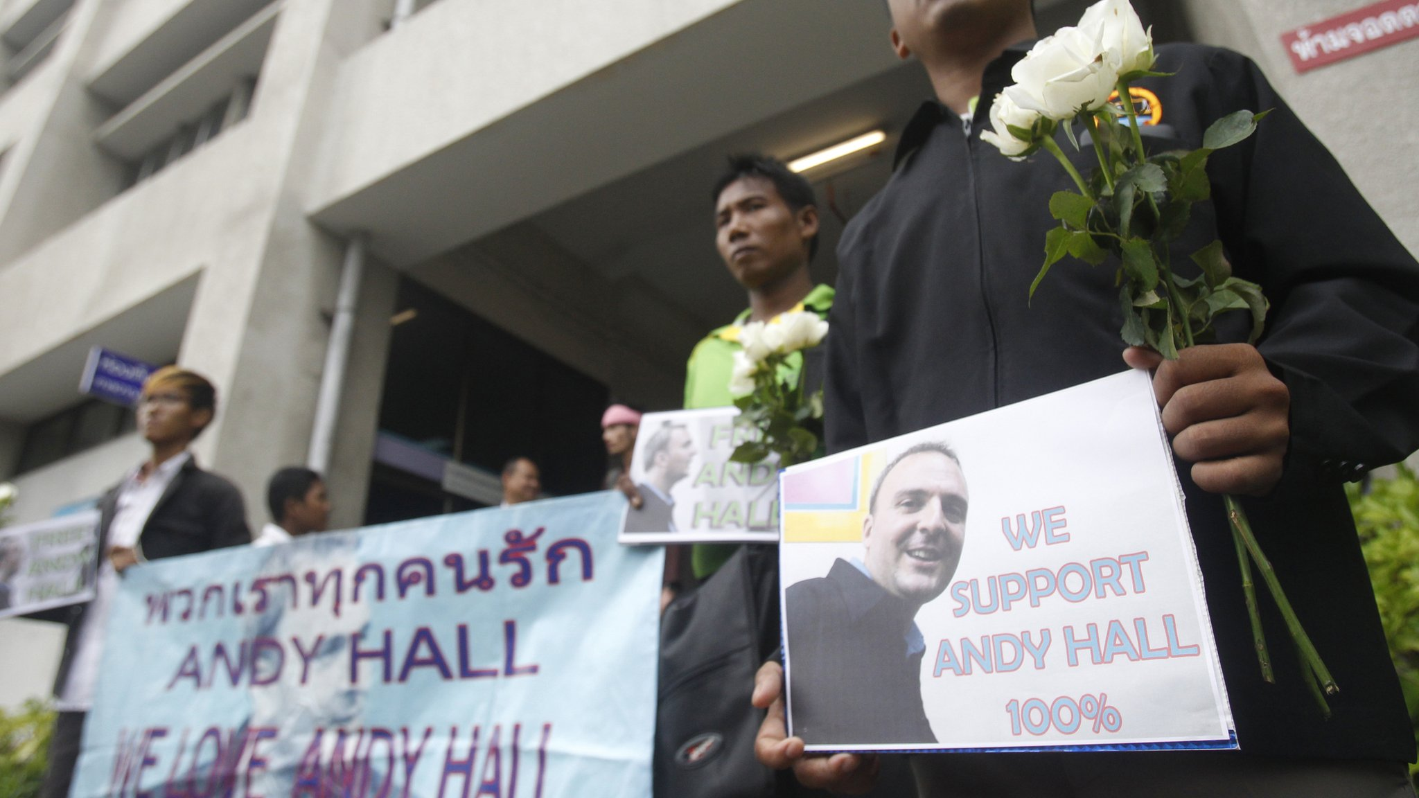 Supporters hold flowers and and placards as the British human rights activist Andy Hall arrives at Bangkok South Criminal Court
