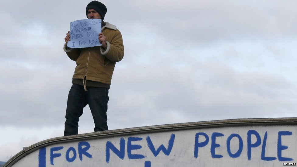 A man holding a sign saying: I am searching for freedom in Europe but I find none