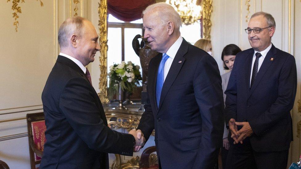 Putin y Biden estrechando manos.