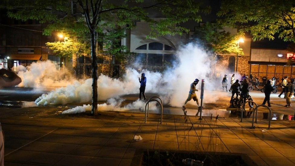Protesters run from tear gas near the Minneapolis Police third precinct