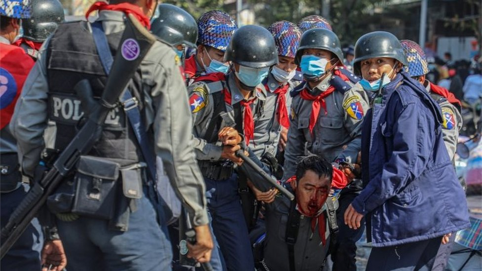 Police carry their injured colleague as people protest against the military coup and demand the release of elected leader Aung San Suu Kyi, in Mandalay, Myanmar, February 9, 2021.