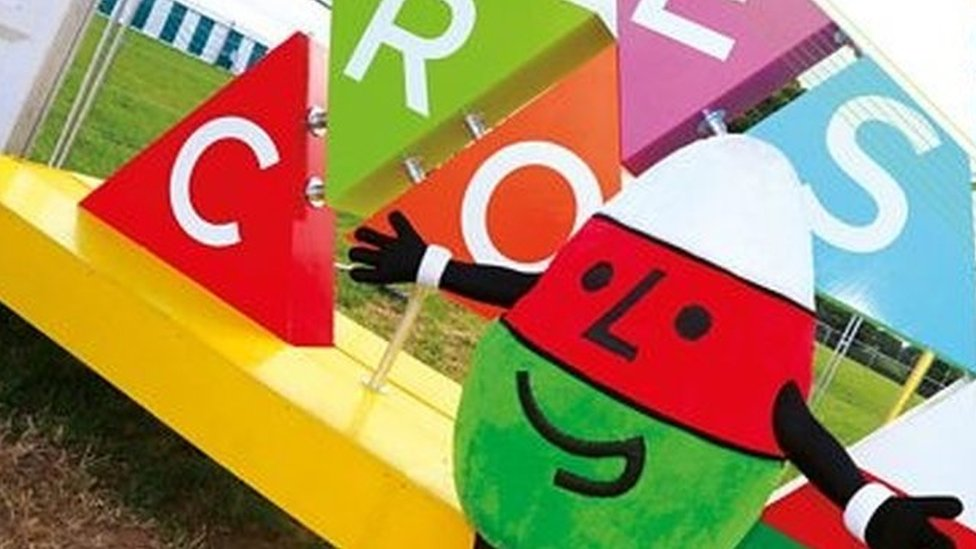 Urdd mascot Mr Urdd standing in front of a creosol (welcome) installation
