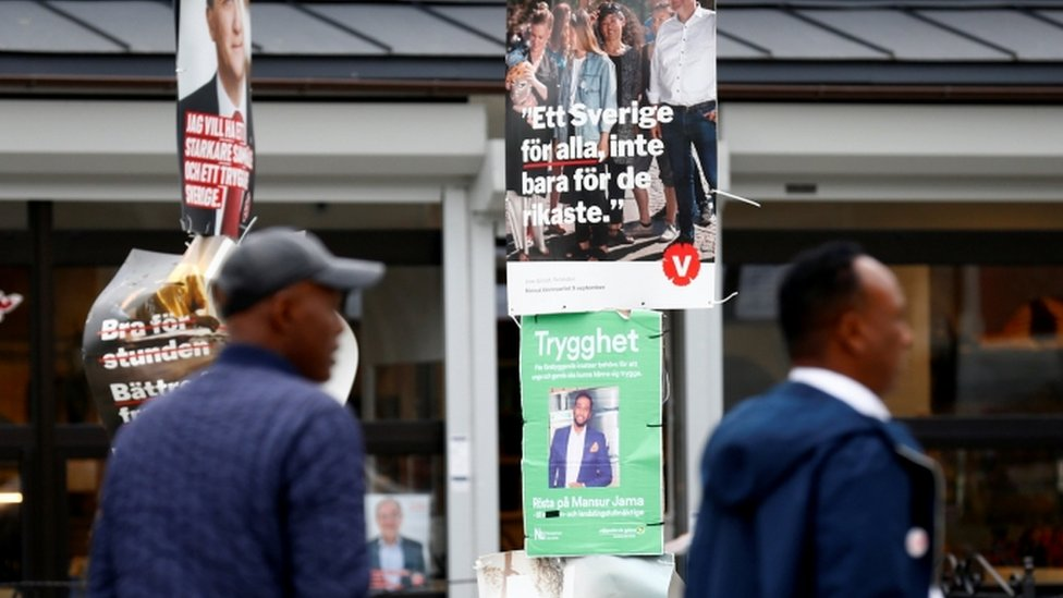 People walk past election campaign posters in Stockholm, 7 September