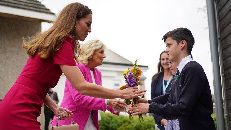 طلاب أكاديمية كونور داونز يقدمون باقتين من الزهور لكاثرين دوقة كامبريدج (يسار) وجيل بايدن سيدة أمريكا الأولى (وسط)