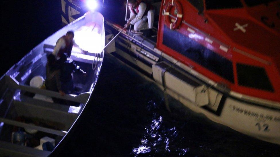 Momento en que un barco rescata a dos pescadores en una lancha
