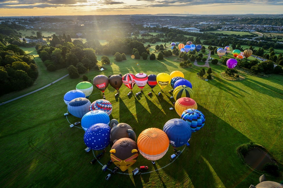 An aerial view of hot air balloons arranged in a heart shape on the ground in Bristol