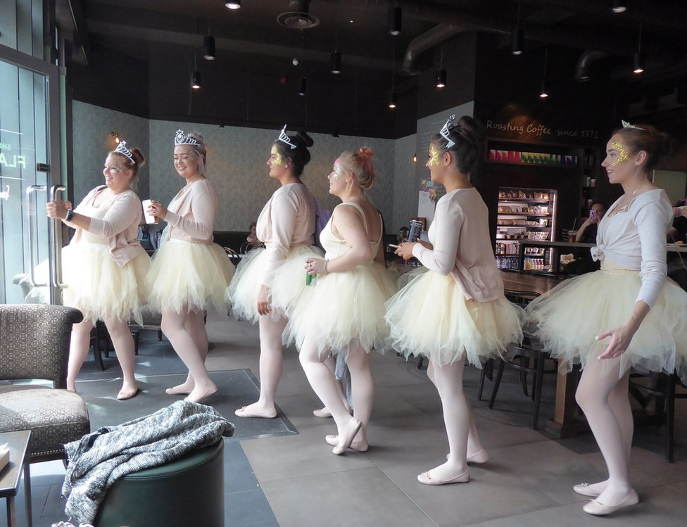 A group of women walking in a line are dressed in ballerina costumes
