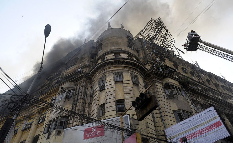 Indian fire-fighters spray water to control a fire on a building in Kolkata on March 23, 2010.