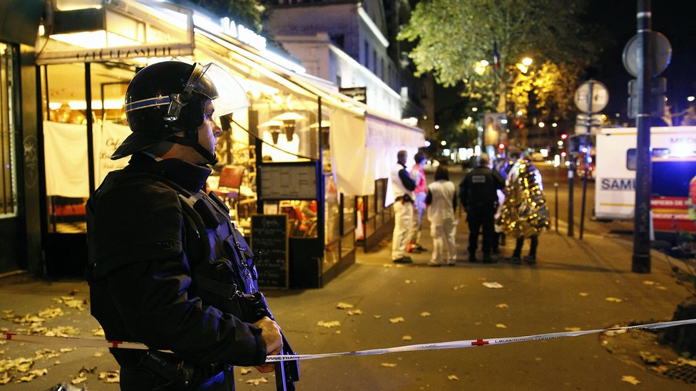 Policeman with gun and tape near Bataclan