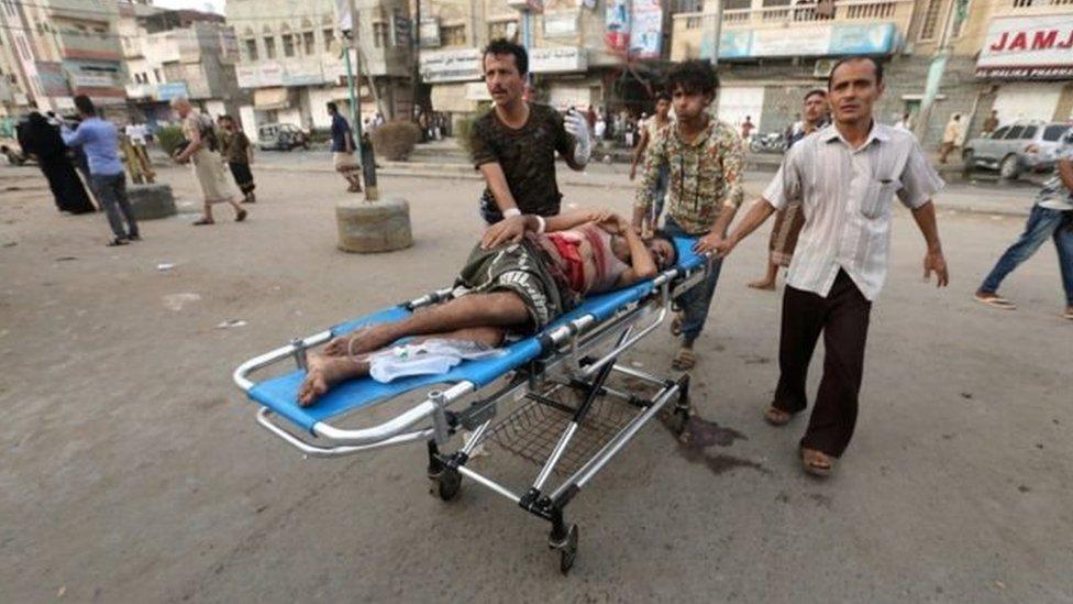 محاولة لإسعاف رجل أصيب في سوق الأسماك في إحدى الهجمات باليمن