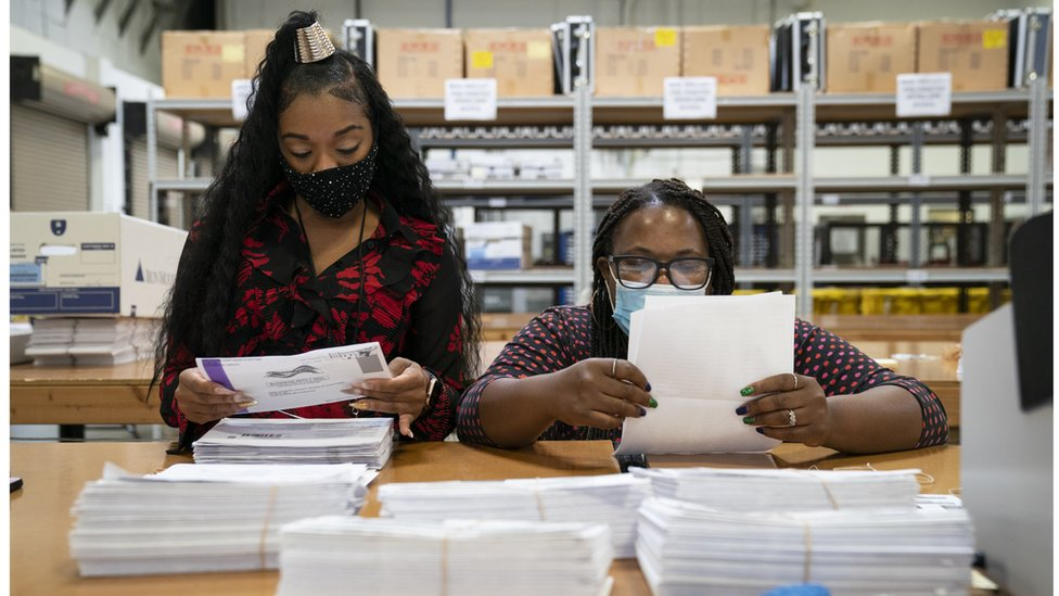 Working in bipartisan pairs, canvassers process mail-in ballots in Maryland, the earliest state to process postal votes in the country