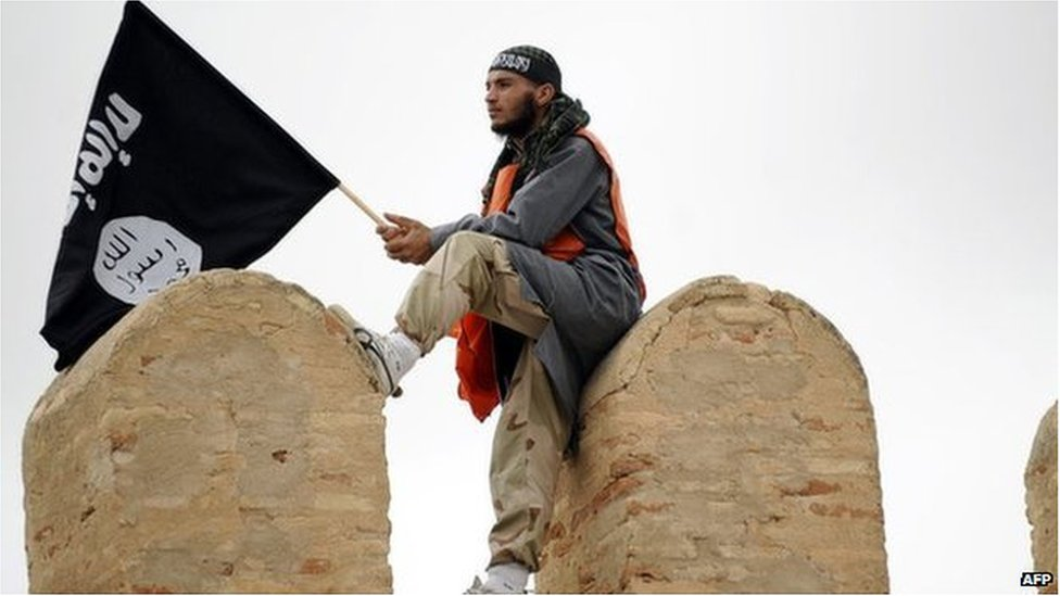 """A Tunisian Islamist waves a Salafist flag reading: """"There is only one God"""" during a rally in May 2012 in Tunisia for the Ansar al-Sharia's national congress"""