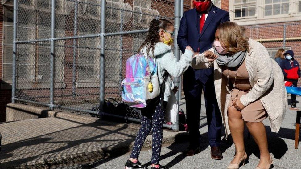 Professora cumprimenta aluna em escola de Nova York, em foto de abril