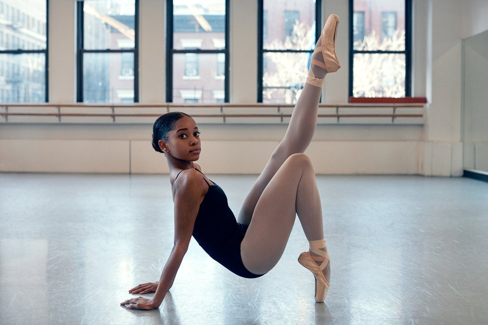 A ballet dancer poses with her leg up on the floor of a dance hall