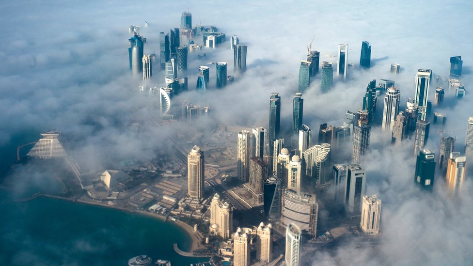 An aerial view of high-rise buildings emerging through fog in Doha, Qatar (15 February 2014)