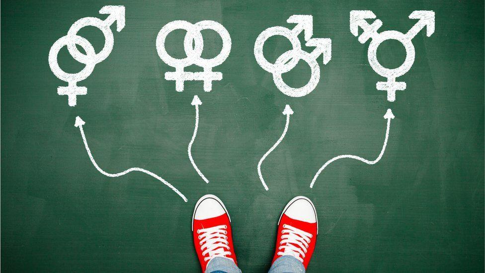 Pies sobre un pizarrón delante de los símbolos de mujer y hombre.