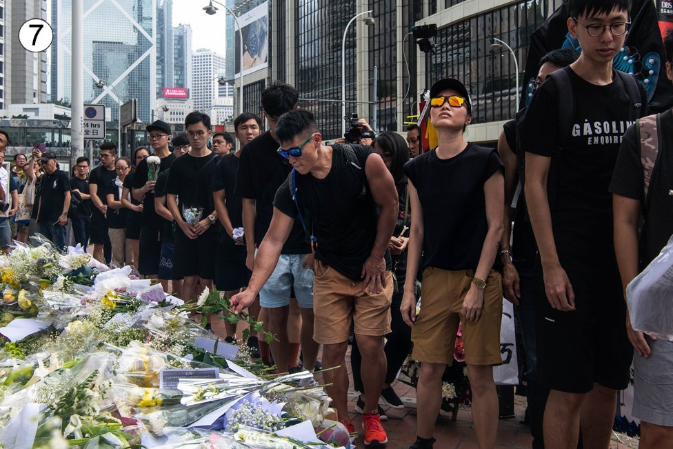 A queue of people dressed in black lay flowers at this site on a busy Hong Kong street