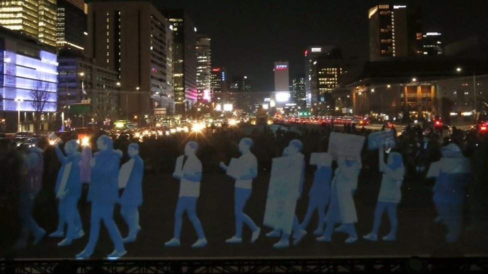Holograms of protesters are shown on a screen during a rally in Seoul. Photo: 24 February 2016