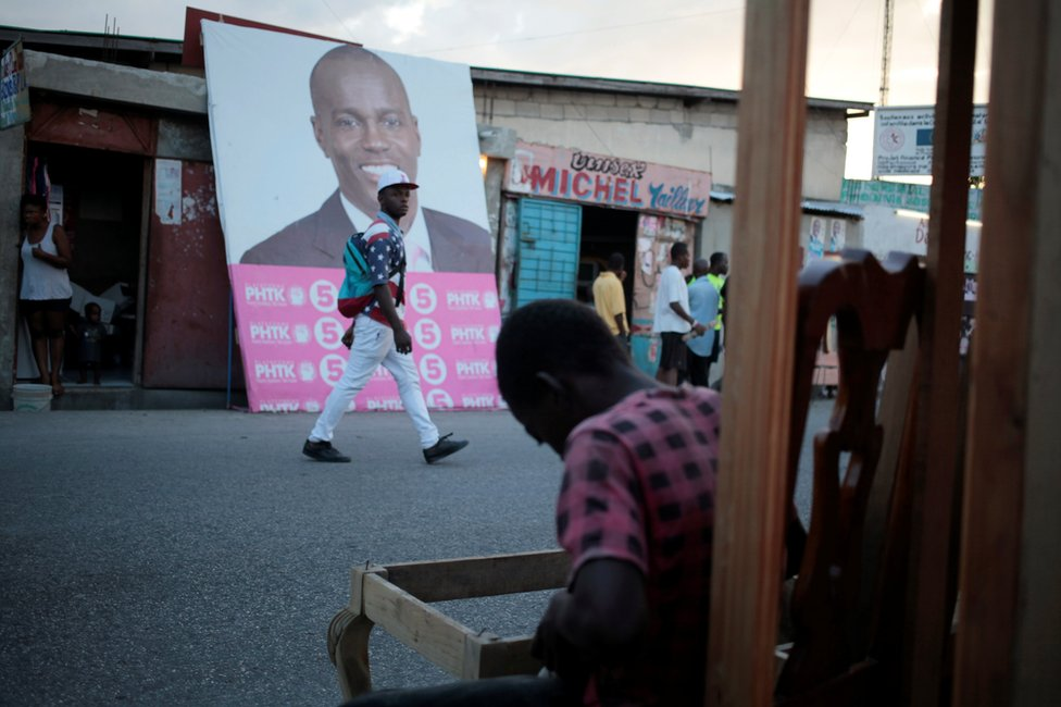 A man walks next to a billboard of presidential candidate Jovenel Moise in Port-au-Prince, Haiti, 17 November