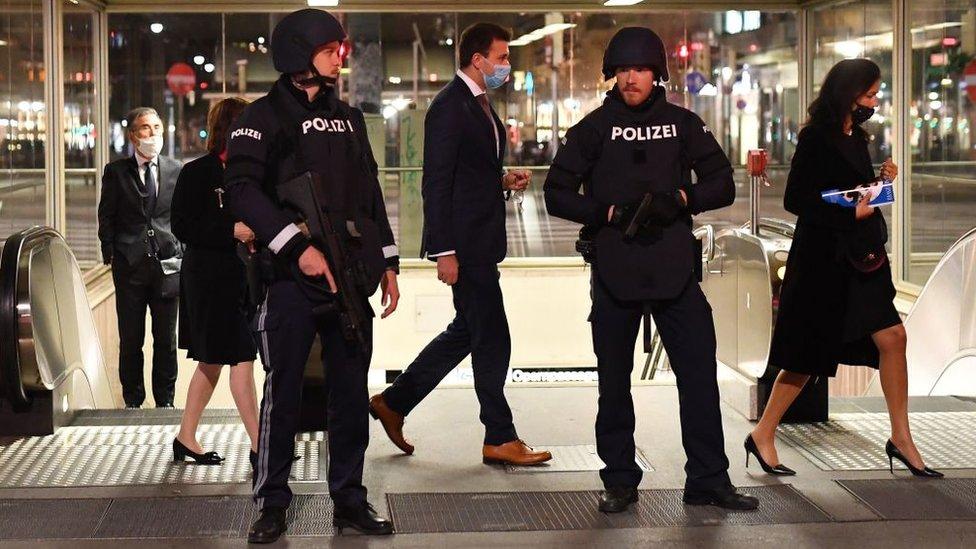 أشخاص يغادرون دار أوبرا فيينا في حراسة الشرطة