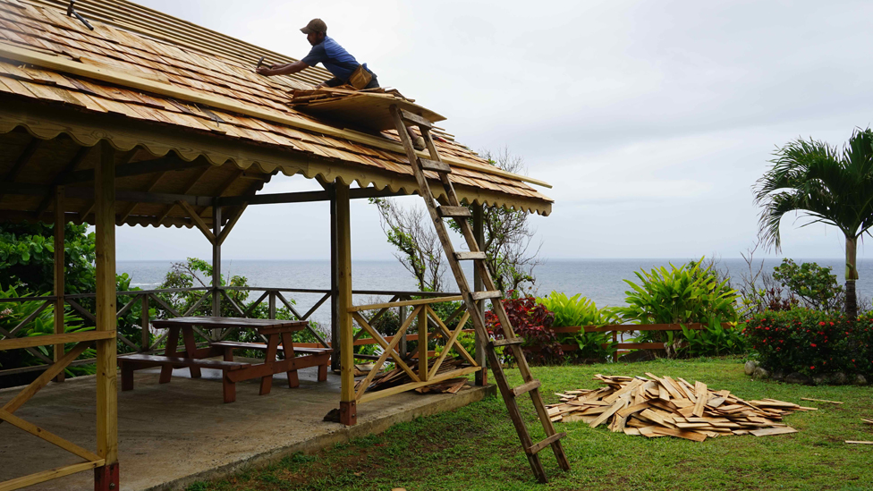 A man fixes the roof in Salybia