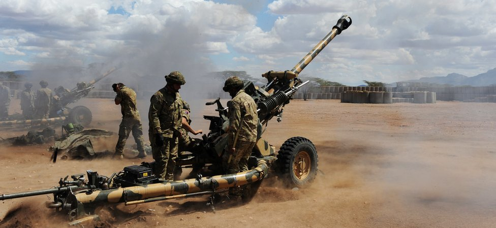 A row of British soldiers fire artillery guns in Kenya