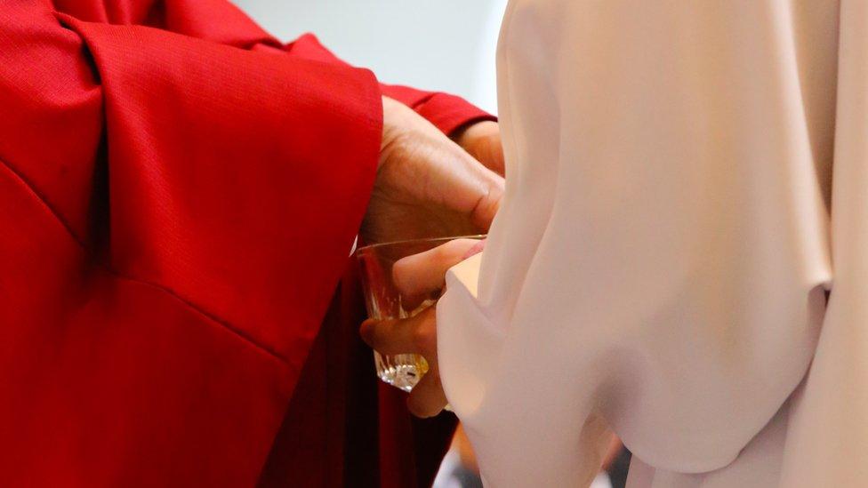 Sacerdote lavándose las manos en una misa.