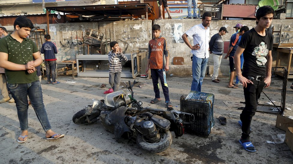 People gather at the site of suicide blasts in Baghda's Sadr City