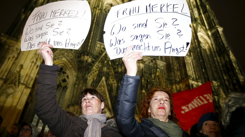 """Women in Cologne hold placards saying """"Mrs Merkel: Where are you? What do you say? This alarms us"""""""