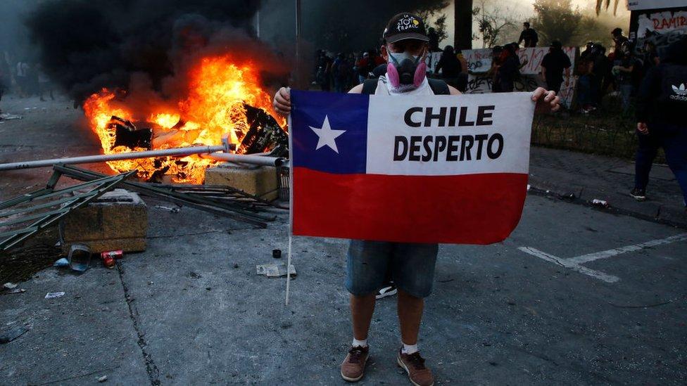 "Un manifestante sostiene una bandera chilena con la frase ""Chile despertó""."