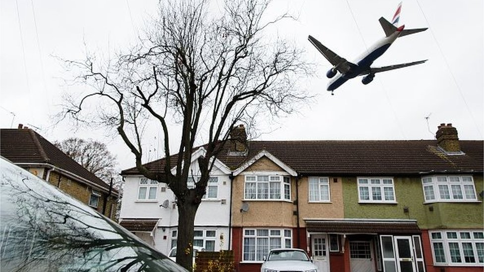 An aircraft flies over residential houses in Hounslow as it prepares to land at London Heathrow