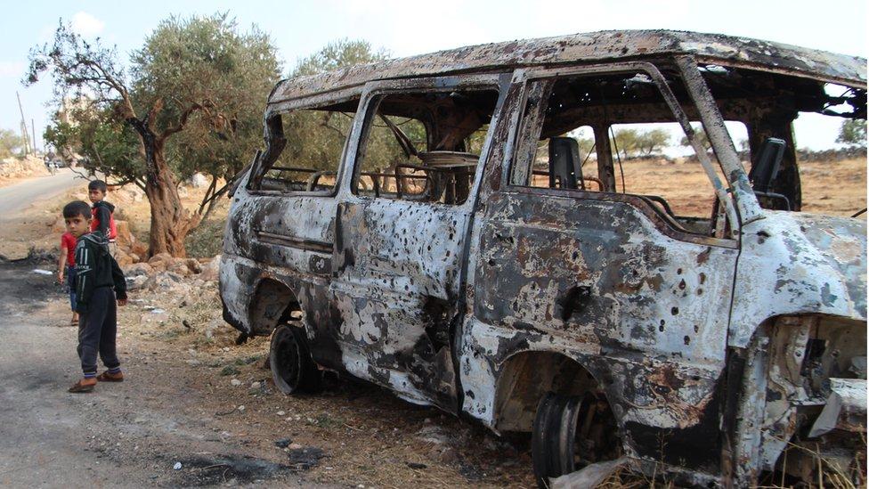 Niños cerca a un bus quemado en Barisha, en el noroeste de Siria.