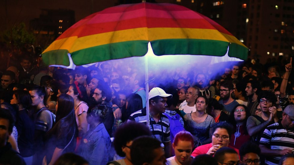 A man holds a rainbow umbrella in a big crowd at an anti-Bolsonaro protest in Sao Paulo on 10 October