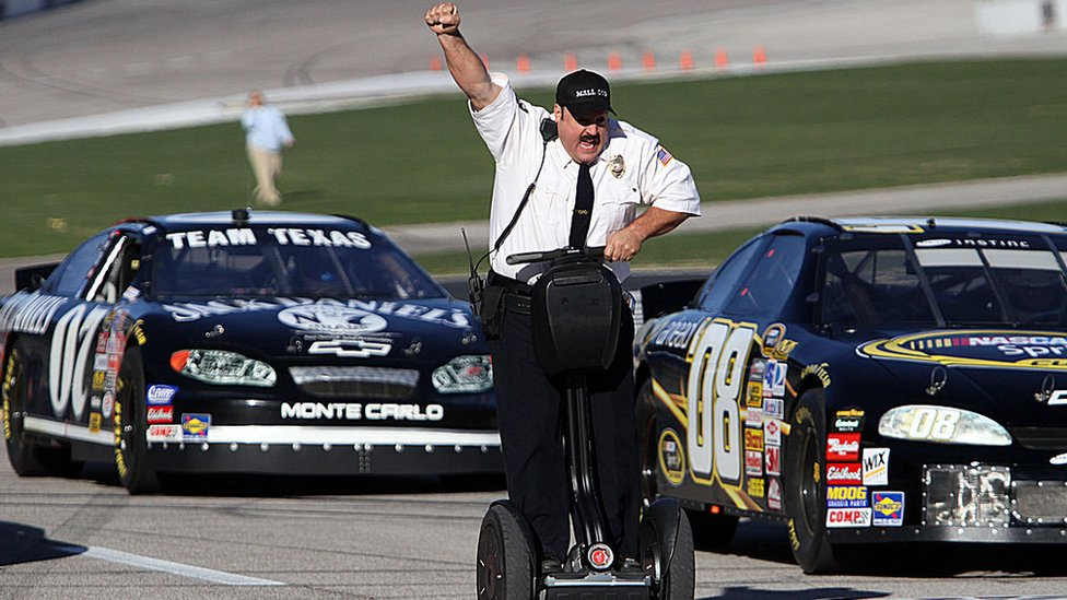 """Actor and comedian Kevin James celebrates while racing NASCAR stock cars with his Segway to promote the release of his new movie, """"Paul Blart: Mall Cop""""."""
