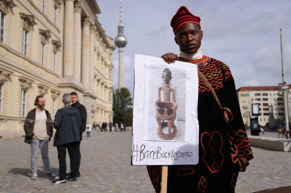 متظاهر من الكاميرون يسعى لاستعادة تمثال نغونسو، يقف خارج منتدى همبولدت أثناء افتتاح متحف همبولدت الإثنولوجي ومتحف الفن الآسيوي. وقفت مجموعة صغيرة من المتظاهرين من الكاميرون خارج منتدى هومبولت للمطالبة بإعادة التمثال، الذي يقولون إنه قطعة أثرية روحية مقدسة، ويزعمون إنها نهبت من قبل ألمانيا في عام 1902 بينما كانت الكاميرون مستعمرة ألمانية