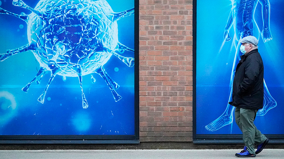 A man wearing a protective face mask walks past an illustration of a virus outside Oldham Regional Science Centre - 24 November 2020