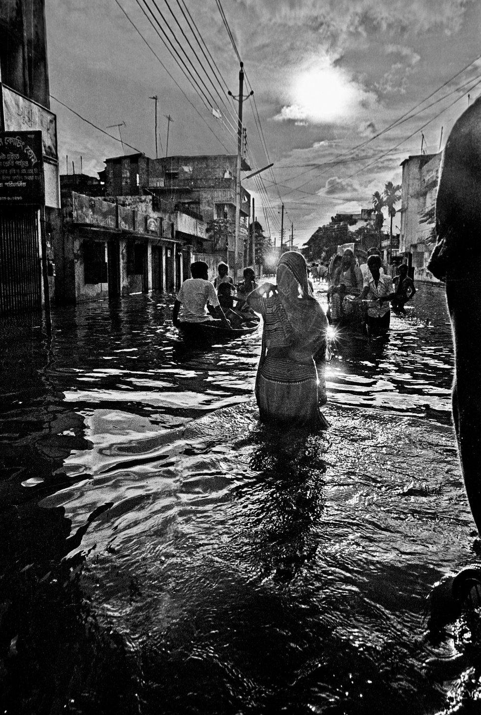 Woman wading in flood, Kamalapur, Dhaka, Bangladesh. 1988.